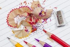 Virutas del lápiz del colorante en un cuaderno de notas alineado Imagen de archivo libre de regalías