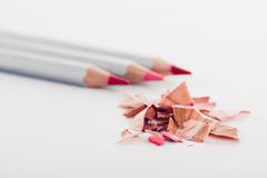 Virutas del lápiz rosado cosmético y de lápices coloreados en el fondo blanco Imágenes de archivo libres de regalías