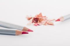 Virutas del lápiz rosado cosmético y de lápices coloreados en el fondo blanco Foto de archivo