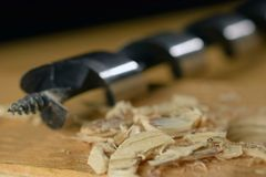Virutas y broca de madera en el tablero de madera fotos de archivo libres de regalías