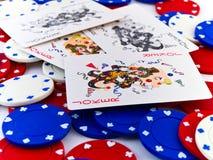 Virutas y bromistas blancos y azules de póker rojas en blanco Foto de archivo