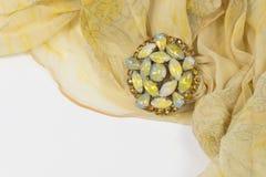 Virvlad runt ren gul blom- halsduk med en tappning cabochon och bergkristallbrosch på vit Royaltyfri Foto