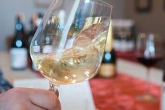 Virvlande runt vitt vin i en vinglas royaltyfri bild