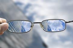 Visão de uma construção de vidro do negócio através dos vidros Fotografia de Stock Royalty Free