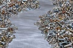 Vis, écrous - et - boulons sur le fond en métal Images stock