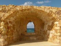 Vis de uma fenda em uma parede de tijolo amarela que separa Chania do mar fotografia de stock royalty free