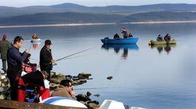 Vis-mens die op het meer vissen stock afbeeldingen
