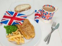 Vis met patat met een kop thee en een brood en boter Royalty-vrije Stock Afbeeldingen