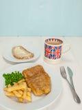 Vis met patat met een mok thee en brood en boter Stock Foto's