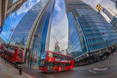 Vis-oog mening met rode dubbele dekbus en nieuwe gebouwen Lond stock foto
