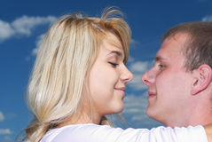 Vis-a-vis. Girl and  young man look against each other enamoured eyes against dark blue sky Royalty Free Stock Images