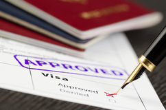 Visa application approved, close up shot of a form, passports and pen. Visa form close up, fountain pen and approved stamped on a document royalty free stock photos