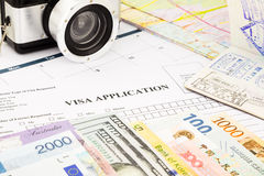 Visa application form, passport, world currency and banknotes. Closeup visa application form, passport, camera and world currency. planning schedule for holiday Stock Images