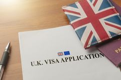 Visa application for uk on desktop with passport and union jack wallet. Visa application on desktop with passport and union jack wallet royalty free stock photo