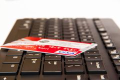 Visa card on a laptop keyboard. The Visa debit card has been used for online payments. Black keyboard. Red visa card Stock Images