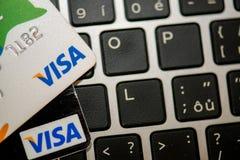 Visa cards laying on laptop. MAY 4, 2015: Two bank credit cards Visa laying on laptop keboard royalty free stock photos