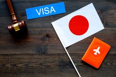 Visa to Japan concept. Text visa near passport cover and japanese flag, hammer on dark wooden background top view royalty free stock images