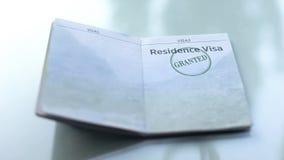 Visa de résidence accordé, joint embouti dans le passeport, bureau de douane, voyageant images stock