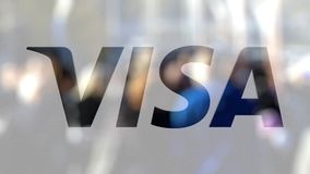 Visa Inc. logo on a glass against blurred crowd on the steet. Editorial 3D rendering. Visa Inc. logo on a glass against blurred crowd on the steet. Editorial 3D stock video footage