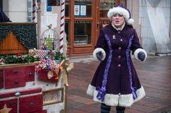 Visa med par av den traditionella musikern och sångaren med den purpurfärgade trolldräkten på julmarknaden Arkivbild