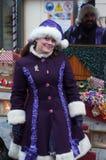 Visa med par av den traditionella musikern och sångaren med den purpurfärgade trolldräkten på julmarknaden Fotografering för Bildbyråer