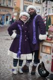 Visa med par av den traditionella musikern och sångaren med den purpurfärgade trolldräkten på julmarknaden Royaltyfri Bild