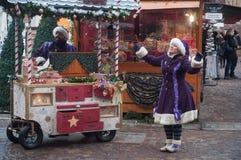 Visa med par av den traditionella musikern och sångaren med den purpurfärgade trolldräkten på julmarknaden Royaltyfria Foton