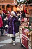 Visa med par av den traditionella musikern och sångaren med den purpurfärgade trolldräkten på julmarknaden Arkivfoto