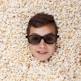 Visa upp den unga pojken i stereo- exponeringsglas som ser ut ur popcorn, grina Arkivbild