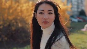 Visage asiatique de tours de femme et regarder la caméra banque de vidéos
