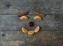 Visage avec la mandarine, l'anis et la cannelle sur le fond en bois Photographie stock