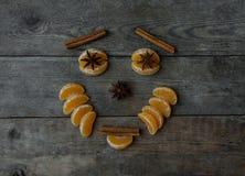 Visage avec la mandarine, l'anis et la cannelle sur le fond en bois Photographie stock libre de droits