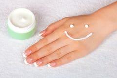 Visage crème de sourire sur la main femelle Photo libre de droits