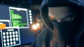 Visage déguisé d'un pirate informatique masculin tout en travaillant dans une fin  clips vidéos