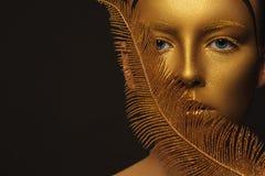 Visage d'or Femme avec le maquillage de luxe d'or Photographie stock libre de droits