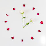 Visage d'horloge fait de pétales de rose blanc au moment de l'exécution d'isolement par concept de fond Photos libres de droits