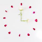Visage d'horloge fait de pétales de rose blanc au moment de l'exécution d'isolement par concept de fond Image libre de droits