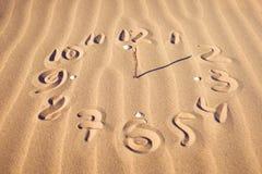 Visage d'horloge sur la plage Photographie stock