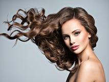 Visage d'une belle femme avec de longs cheveux de vol image stock