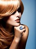 Visage d'une belle femme avec l'anneau de bijoux de saphir sur le doigt photographie stock