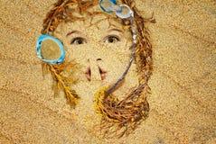 Visage dans le sable image stock