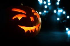 Visage découpé de potiron rougeoyant Halloween sur le fond bleu de lumière de bokeh Photographie stock libre de droits