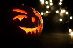 Visage découpé de potiron rougeoyant Halloween sur le fond de lumière de bokeh Photo libre de droits