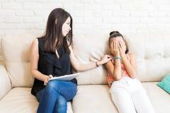 Visage de bâche de Consoling Sad Girl de psychologue sur le sofa photos stock