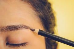 Visage de beauté de femme asiatique en appliquant le crayon de sourcil et la peau lisse par des cosmétiques photos stock