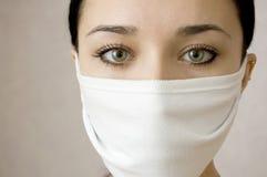 Visage de belles femmes dans un masque médical Image stock