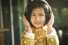 Visage de bonheur de la musique de écoute d'enfants asiatiques dans le téléphone principal photographie stock libre de droits
