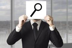 Visage de dissimulation d'homme d'affaires derrière la loupe de loup de signe Photographie stock libre de droits