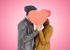 Visage de dissimulation de couples derrière le coeur orange Image stock