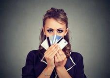 Visage de dissimulation de femme sérieuse derrière beaucoup de cartes de crédit photos stock